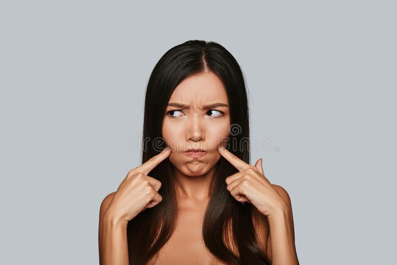 In a bad mood. Displeased young Asian woman making a face while standing against grey background royalty free stock photo