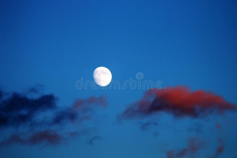 Bad Moon Rising. Early moonrise, when the setting sun still lights up the bloody light of the cloud royalty free stock photo