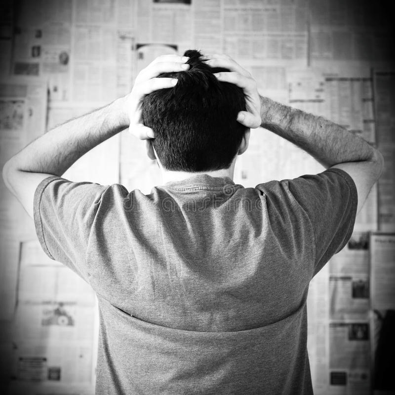 Bad news. Young man overwhelmed with bad news with hands on his head in distress royalty free stock images