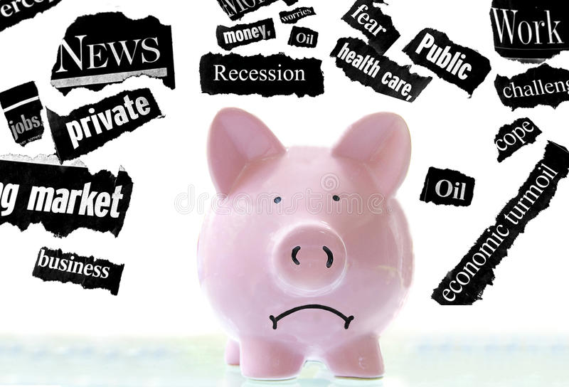 Bad news. Frowning pink piggy bank with bad economic news headlines royalty free stock photography