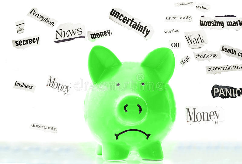 Bad news. Frowning pink piggy bank with bad economic news headlines stock photography