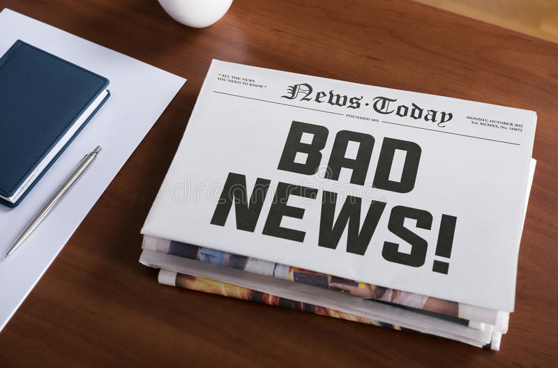 Bad news. Newspaper concept with hot topic Bad news lying on office desk stock image