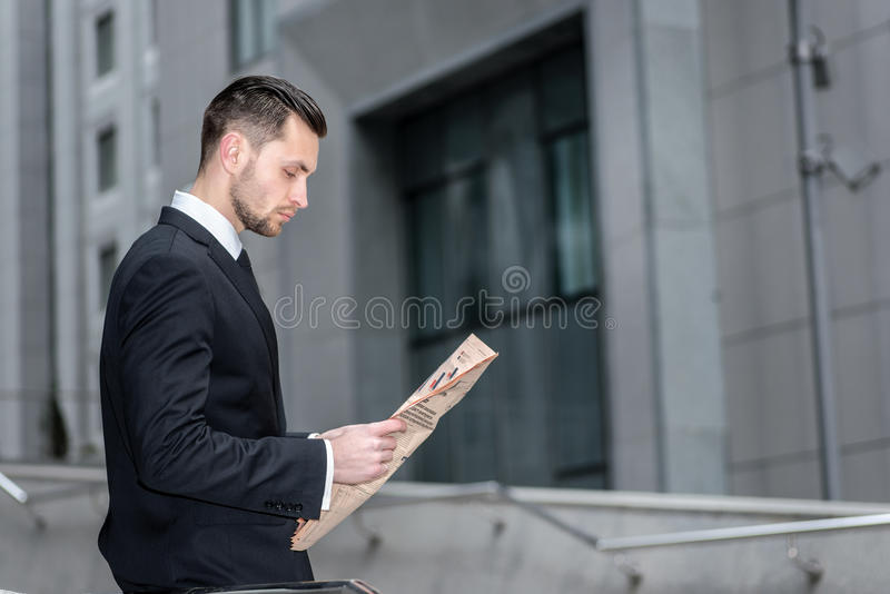 Bad news. Side view of a businessman reading a newspaper that Finance. Bearded man reading business news. royalty free stock images