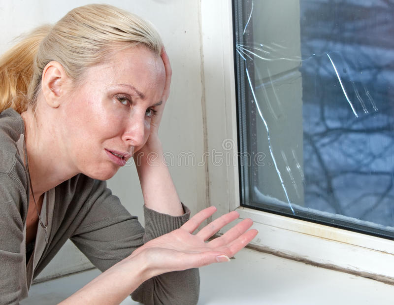 Bad quality double-glazed window. The housewife cries, bad quality double-glazed window has burst because of cold weather royalty free stock photos