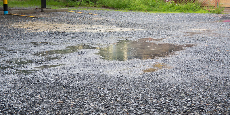 Bad quality road. With potholes and puddles royalty free stock image