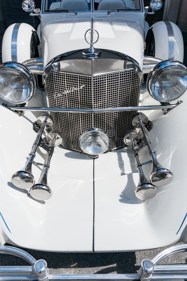 Radiotor and headlights of a classic white Excalibur convertible sports car. Bad Ragaz, SG / Switzerland - 23 June, 2019: radiotor and headlights of a classic stock image
