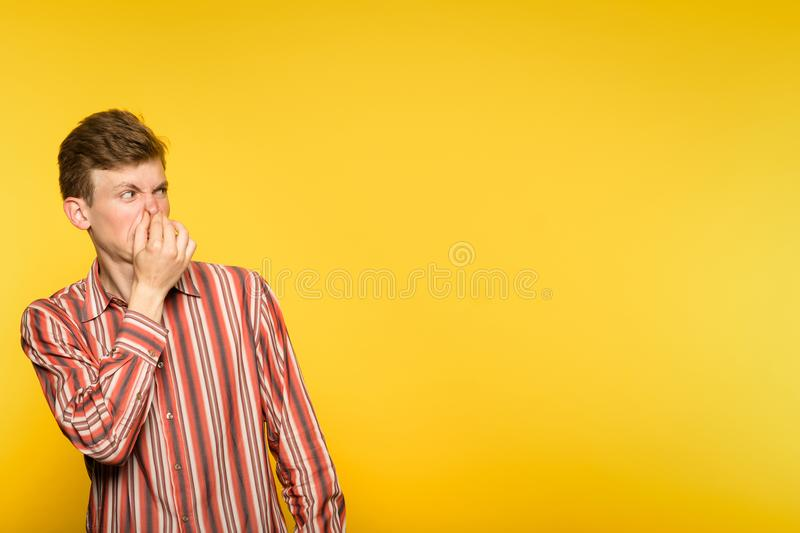 Bad rancid foul smell odour man coveing nose stock photo