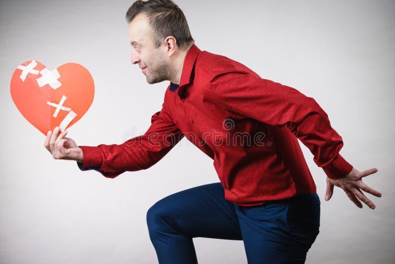 Adult man holding broken heart running royalty free stock images