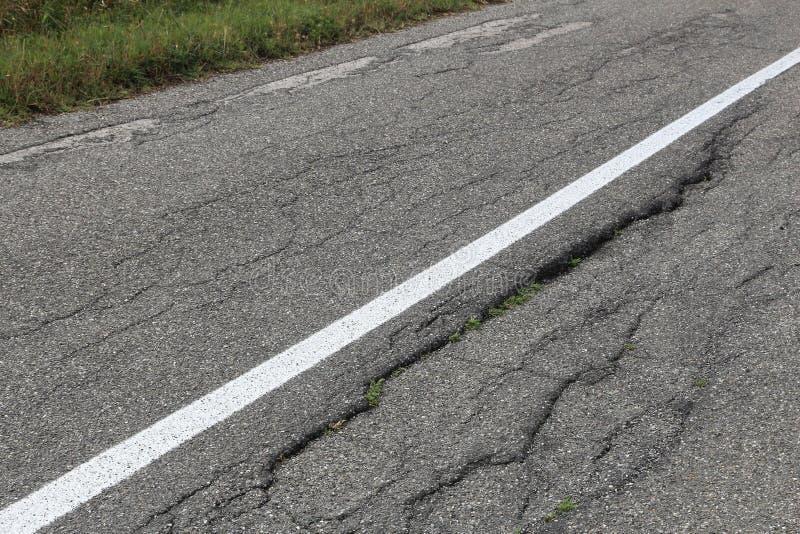 Bad road surface. Road surface damage - bad maintenance quality. Asphalt cracks in Italy royalty free stock photos
