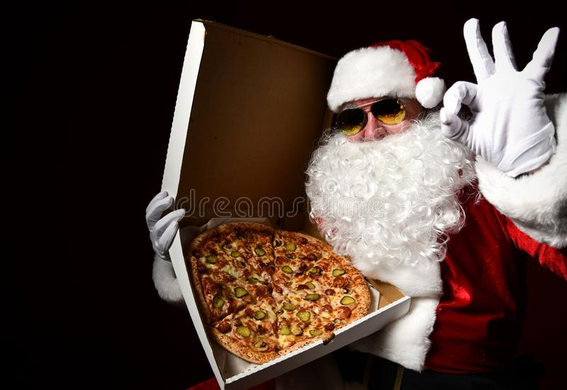 Bad Santa Claus in sunglasses holding opening big hot original pizza smelling offering show ok sign. New year and Merry Christmas. Fast food concept royalty free stock images