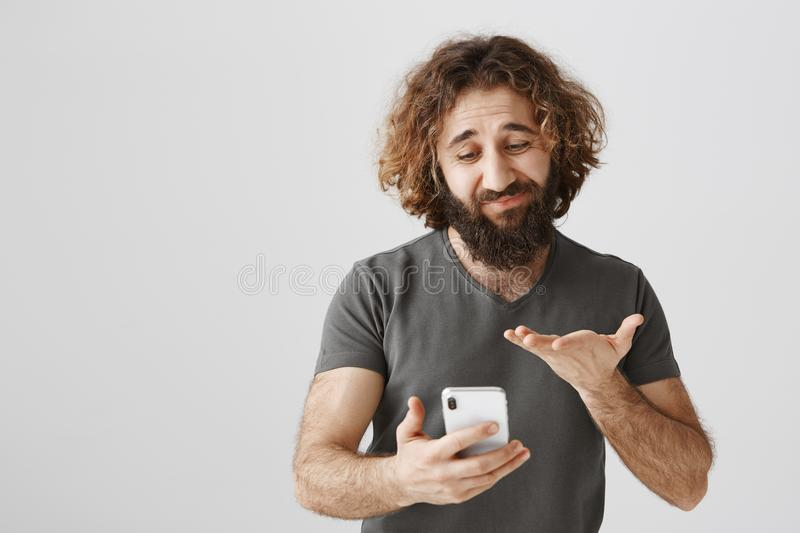 Bad selfie causes unhappy mood. Studio shot of displeased and gloomy eastern man with messy hair and beard holding. Smartphone and gesturing with palm, being stock photography