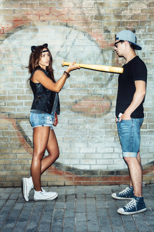 Bad young woman with leather cat ears threatening baseball bat guy. Bad young women with leather cat ears threatening baseball bat guy. Urban scene. Outdoor royalty free stock photos