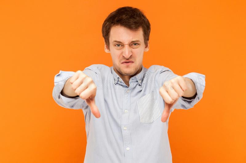 Bad sign. Man showing dislike at camera and have sadness look. Studio shot, orange background royalty free stock images