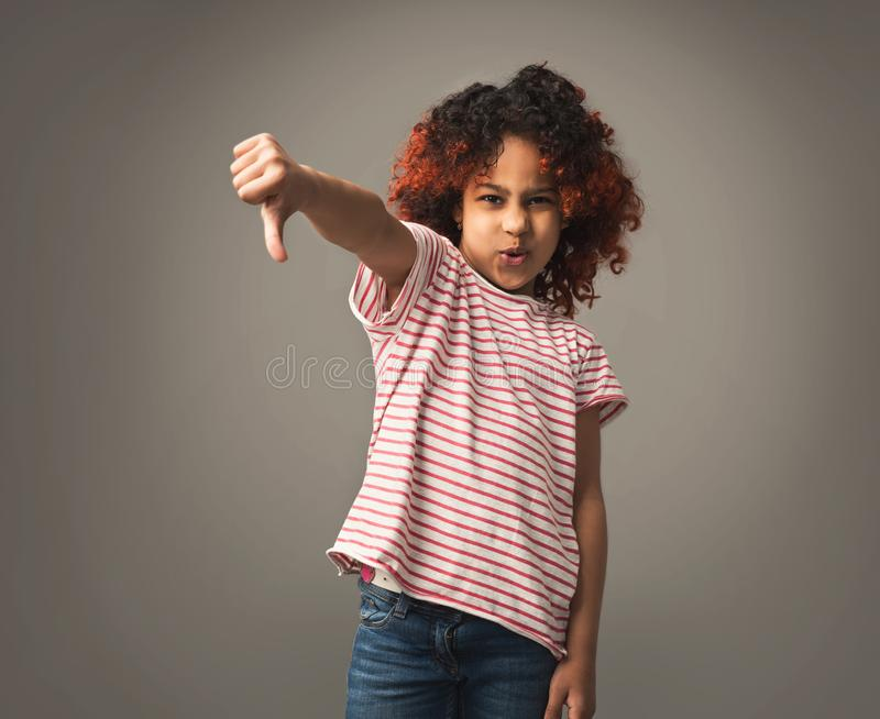 Angry african child girl showing thumb down royalty free stock photography