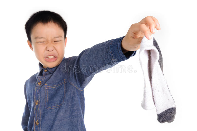 Bad smell sock. Boy feeling unhappy with bad smell white sock stock photos