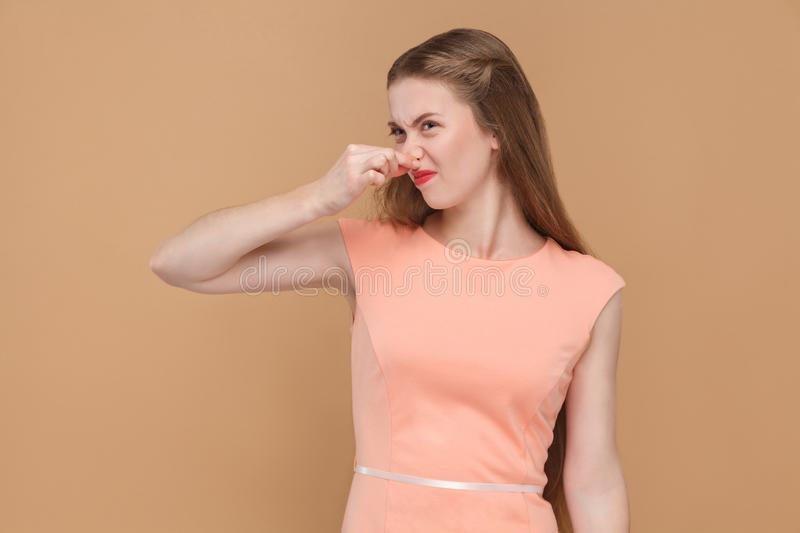Bad smell, unhappy woman holding her nose. stock image
