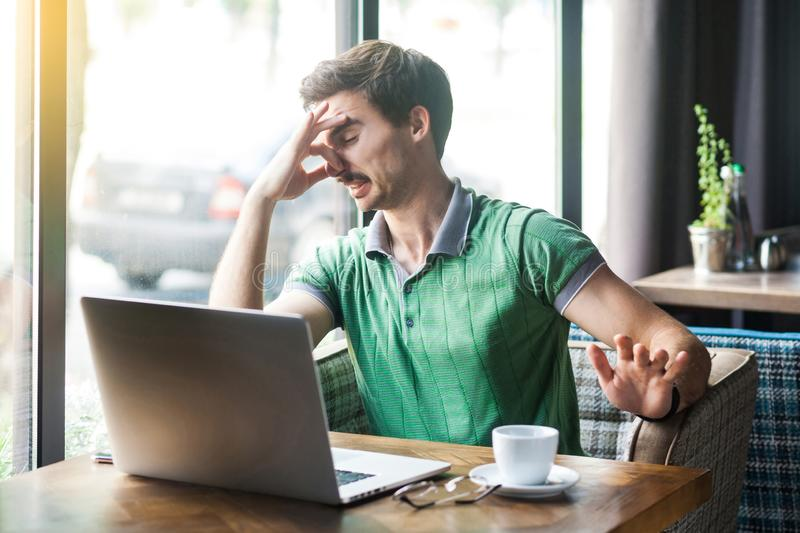 Bad smell. Young dissatisfied businessman in green t-shirt sitting and working on laptop, pinching his nose with negative emotion. Business and freelancing royalty free stock photography