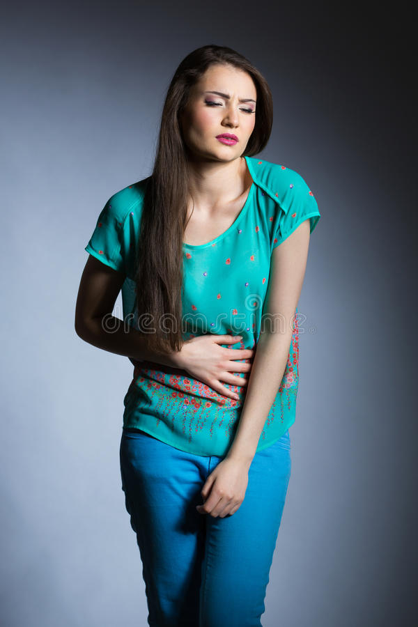 Bad stomachache. A photo of young woman suffering from stomachache. She's keeping one hand on her stomach and cowering a bit. She's wearing in blue stock photography