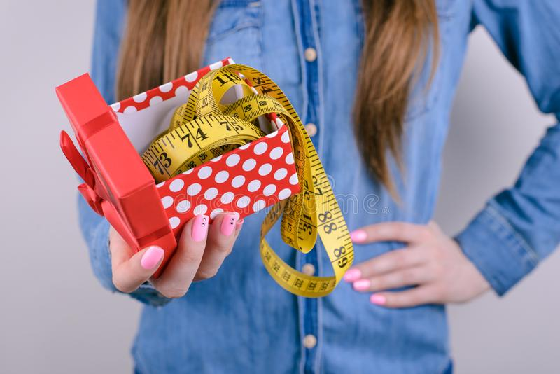 Bad unwanted unwished gift for people lady person concept. Cropped closeup photo of disappointed confused frustrated student. Holding showing tape measure in royalty free stock photos