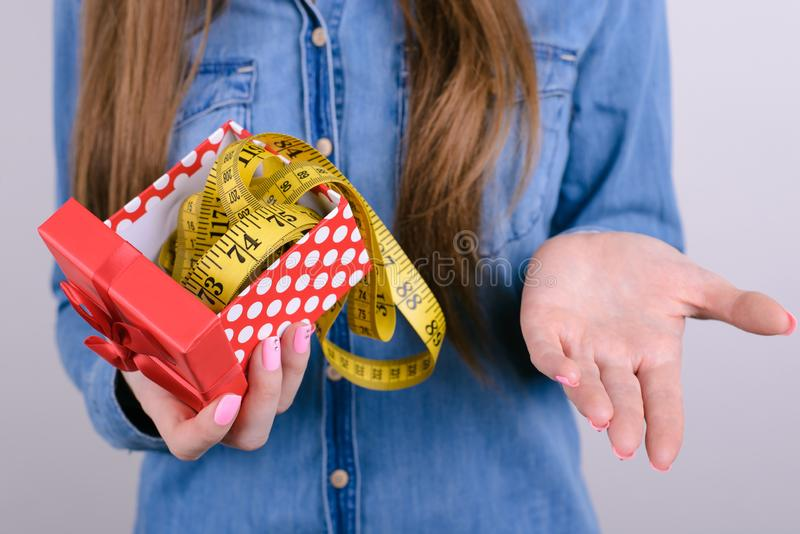 Bad unwanted unwished gift for people lady person concept. Cropped closeup photo of disappointed confused frustrated student. Holding showing tape measure in royalty free stock images