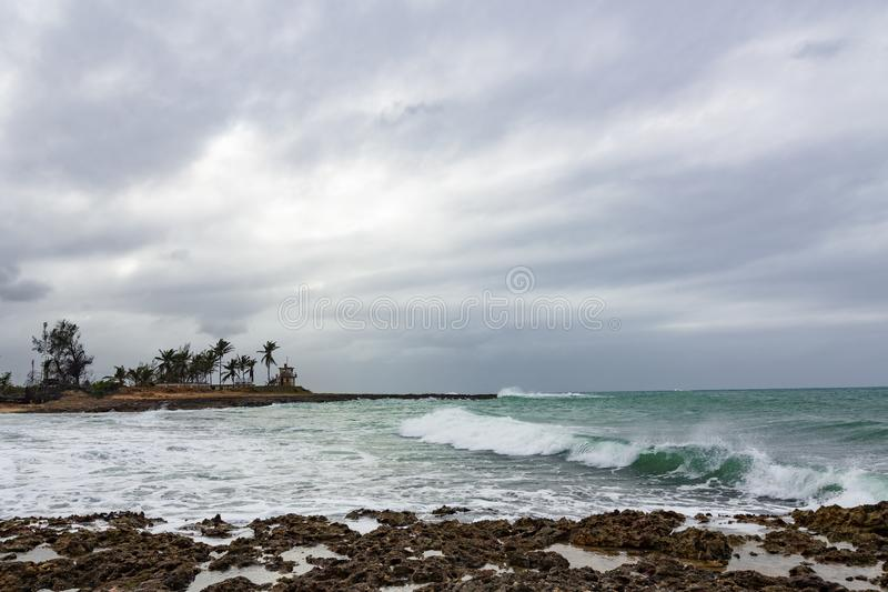 Bad weather seascape with cloudy sky and water wave. Palm trees and a coast house on the background royalty free stock photo