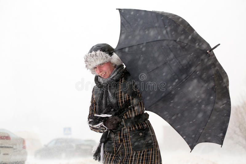 Girl with umbrella during snow storm stock images