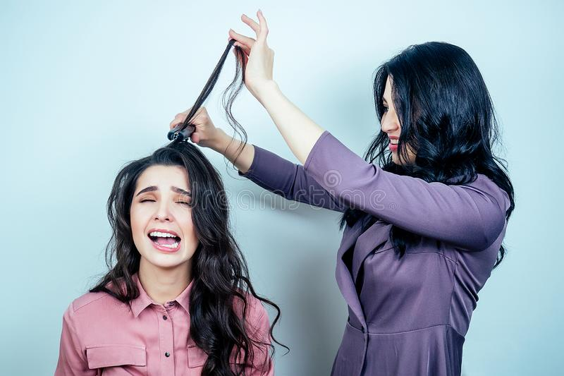 Bad woman hairdresser spoiled hair of unhappy sad client girl in a salon. concept of unprofessionalism and a bad beauty. Bad women hairdresser spoiled hair of stock images