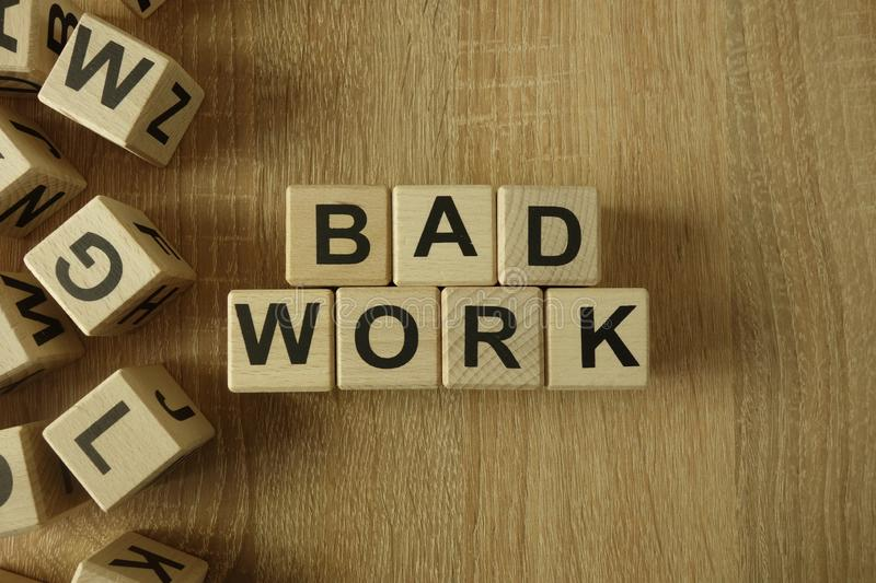 Bad work text from wooden blocks. On desk stock image