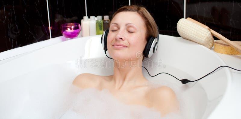 bada den lyssnande musik kopplade av kvinnan för bubblan arkivbild