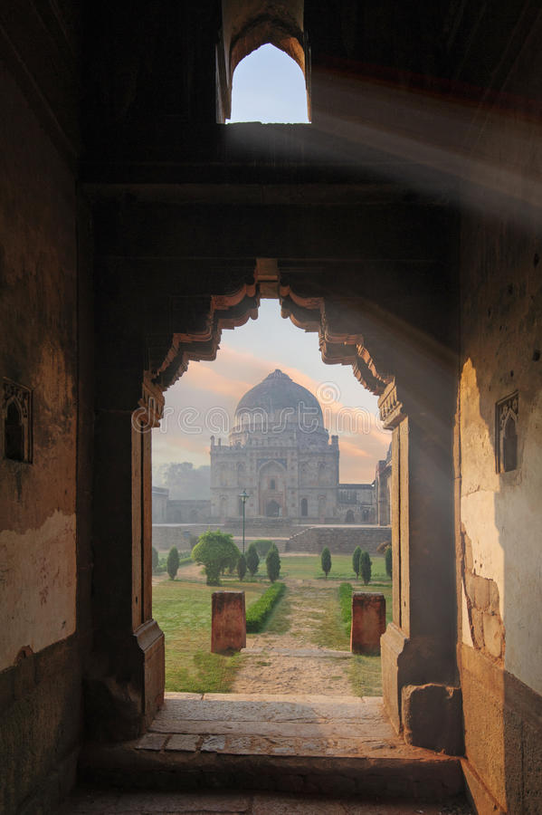 Bada Gumbad Complex at early morning in Lodi Garden Monuments. View through window, Delhi, India stock photos