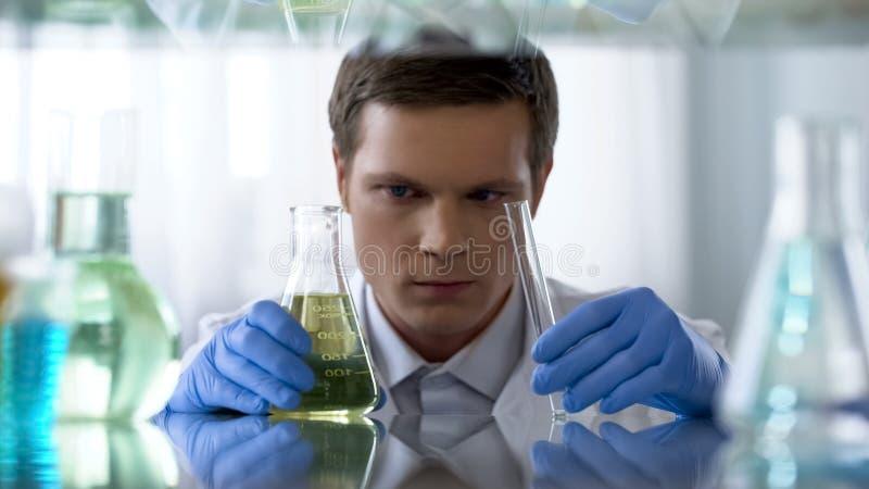 Badacz egzamininuje ciekłego produkt przerobu ropy naftowej, prowadzi laboranckich testy, nauka obraz stock
