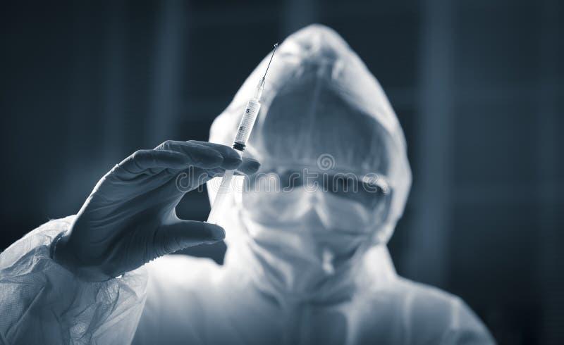 Badacz w ochronnym kostiumu przygotowywa strzykawkę zdjęcie royalty free
