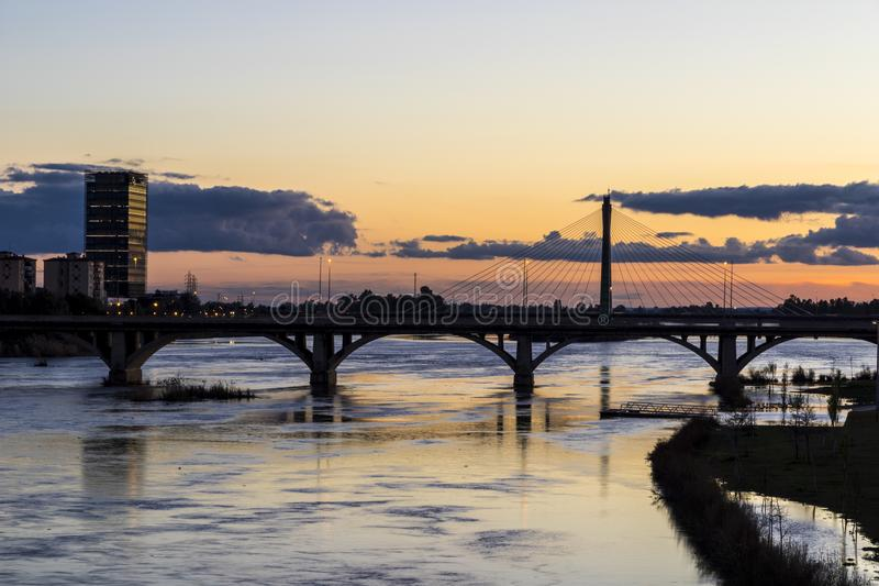 Badajoz, Spain. Views at sunset of river Guadiana, the Torre Caja Badajoz tower, and the Puente Real Royal Bridge, from the Puente de Palmas bridge stock images