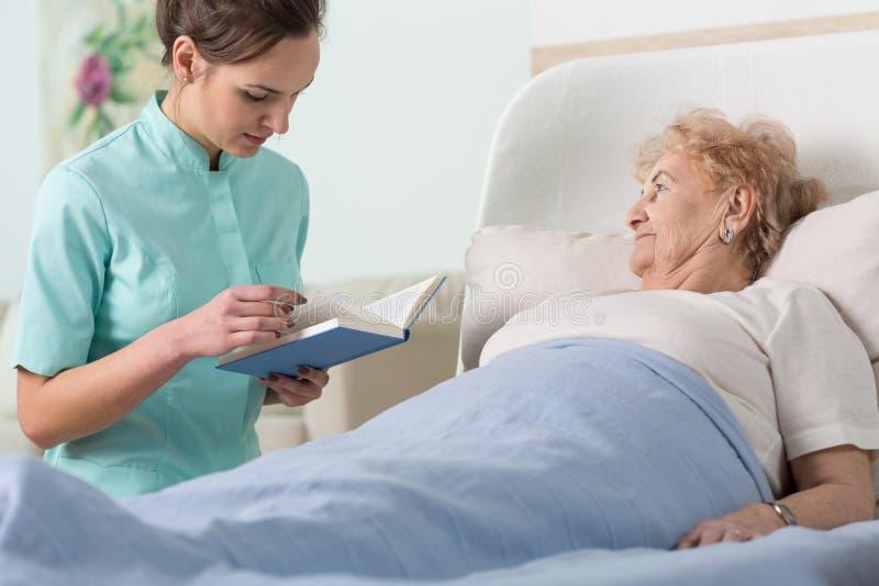Badante che legge libro paziente malato immagini stock libere da diritti