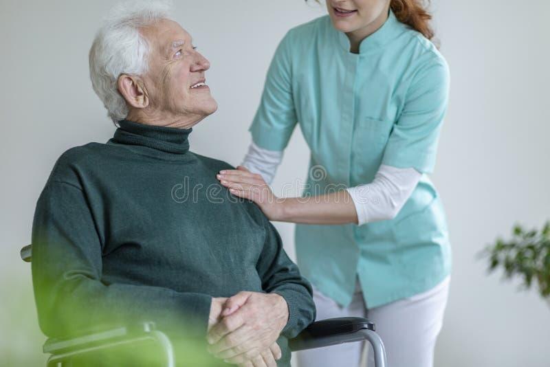 Badante che parla con uomo felice in una sedia a rotelle in una professione d'infermiera uff immagini stock