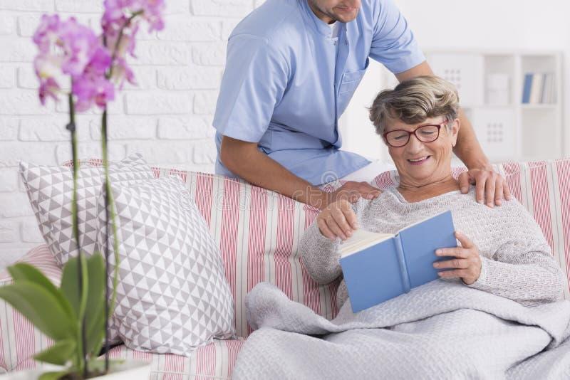 Badante con l'anziano che legge un libro fotografia stock