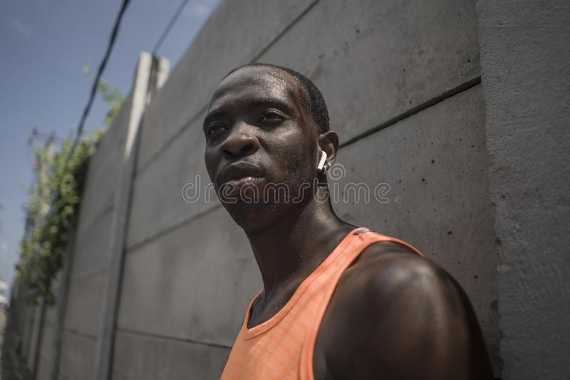 Badass style portrait of young attractive and athletic black afro American sport man in running singlet looking cool on concrete royalty free stock image