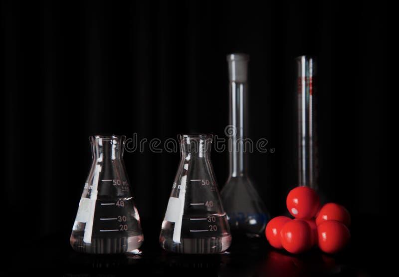 Badawczej nauki szklane kolby z wodnym i czerwonym chemicznym cząsteczkowej struktury wciąż życia edukacji czerni tłem obrazy stock