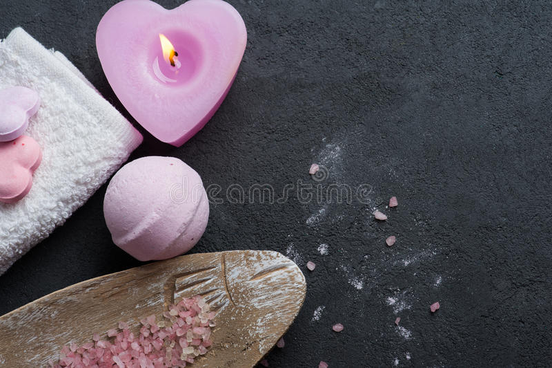 Badebombenahaufnahme mit rosa brennender Kerze stockfoto