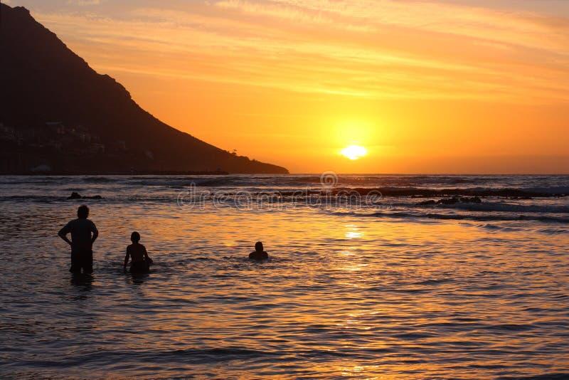Badegäste am Sonnenuntergang, Gordons Schacht, Kapstadt lizenzfreie stockbilder