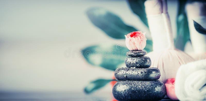 Badekur mit Stapel schwarzen Massagesteinen, Blumen und Tüchern, Wellnesskonzept lizenzfreies stockbild