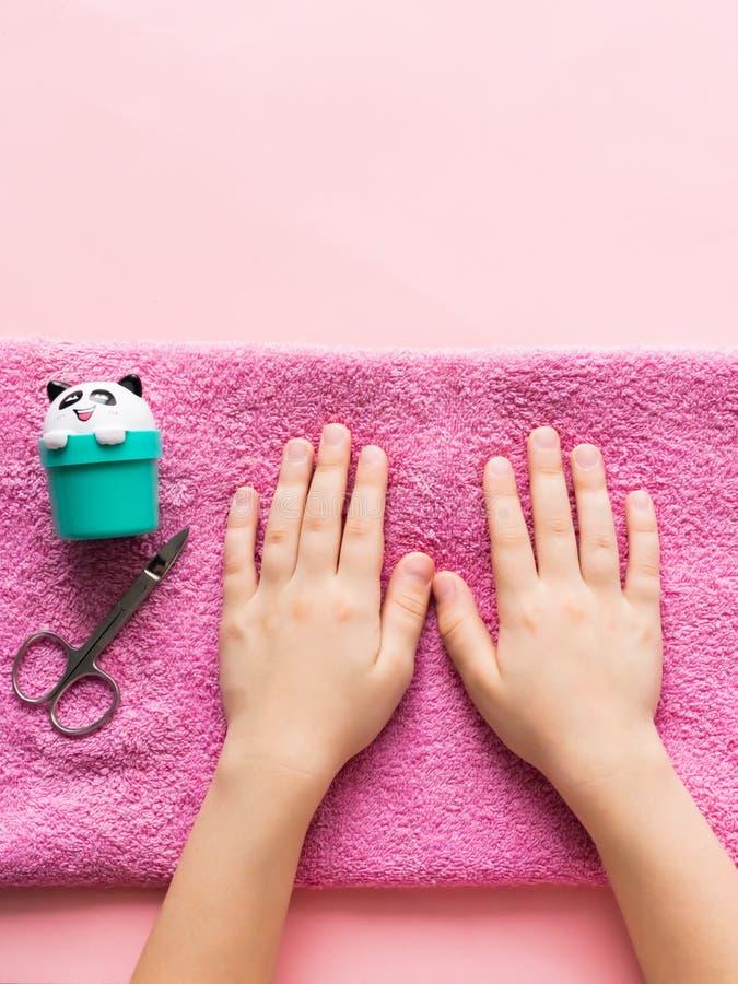 Badekuren für Handhaut und -nägel für Kinder Die Hände des Jungemädchens sind auf rosa weichem Tuch Schönheit und Sorgfaltkonzept lizenzfreies stockbild