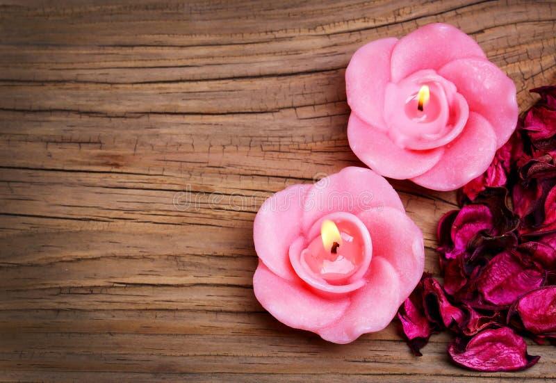 Badekurort. Brennende Kerzen in Form Rosen mit Pfingstrose trockneten Blätter stockfoto