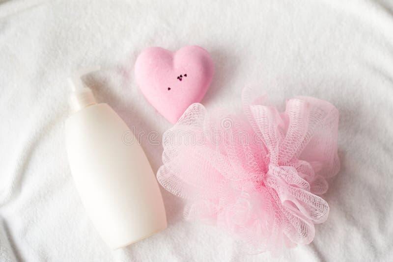 Badekurort im rosa Farbkonzept auf weißem Hintergrund weiße Flasche, flache gelegte Art lizenzfreie stockfotos