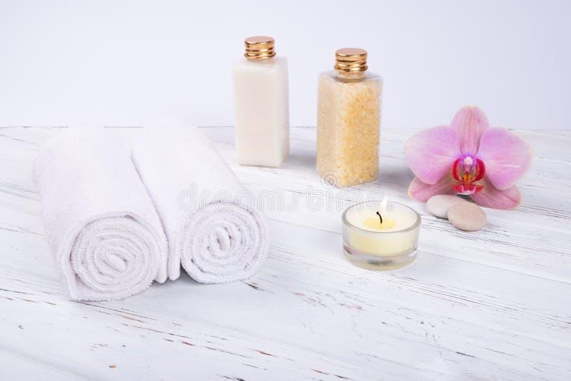 Badekurort-, Sch?nheits- und Wellnessprodukte: Creme, Seesalz, T?cher, verziert mit Orchideenblume und Kerze mit Kopienraum stockfotografie