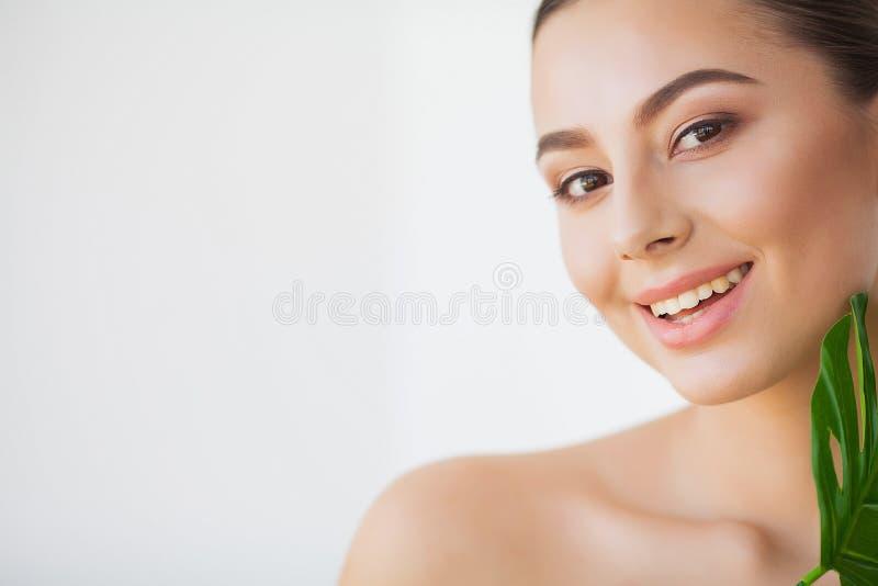 BADEKURORT-Sorgfalt Junge hübsche brunette Frau mit großem grünem Blatt lizenzfreies stockbild