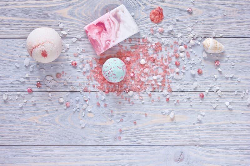 Badekurort- und Duschzubehör Badebomben, Aromatherapiesalz, handgemachte Stück Seife und Muscheln auf hölzernem Hintergrund stockfotos