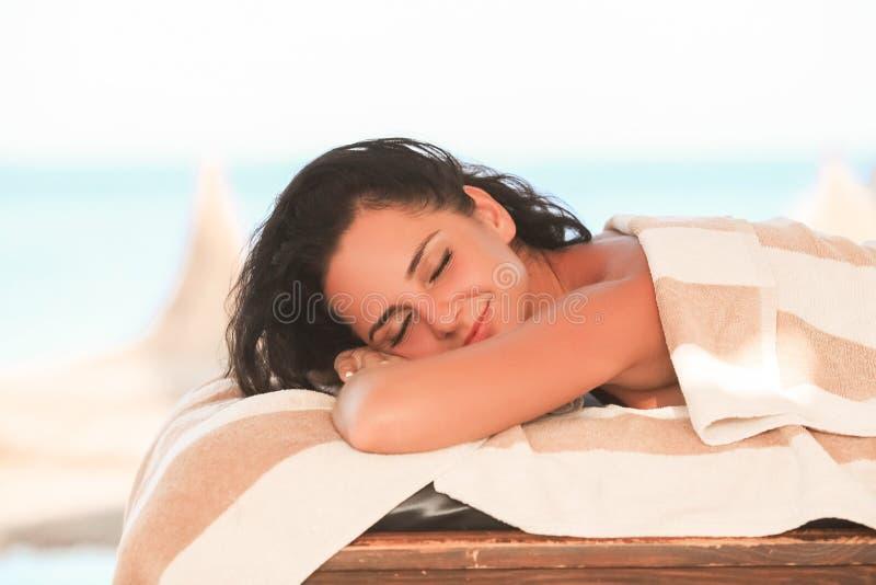Badekurort und Massage Hübsche Frau im Badekurortsalon im sonnigen Strand erhalten Fa lizenzfreie stockfotos