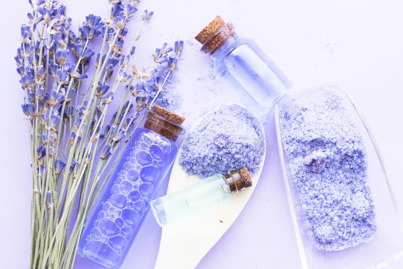Badekurort und Wellnesseinstellung mit Lavendelblumen, Seesalz, ?l in einer Flasche, Aromakerze auf h?lzernem wei?em Hintergrund stockbild