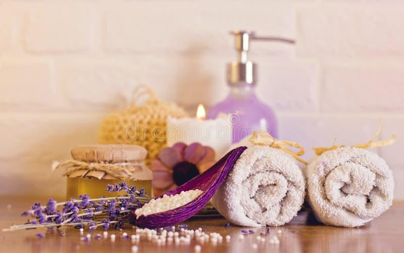 Badekurort und Wellnesseinstellung mit weißen Tüchern, Schwamm, Kerze, Toilette lizenzfreies stockbild